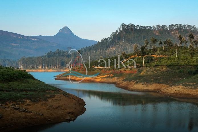 Mountain Adam's Peak at sunset with reflection in the lake. Sri Lanka